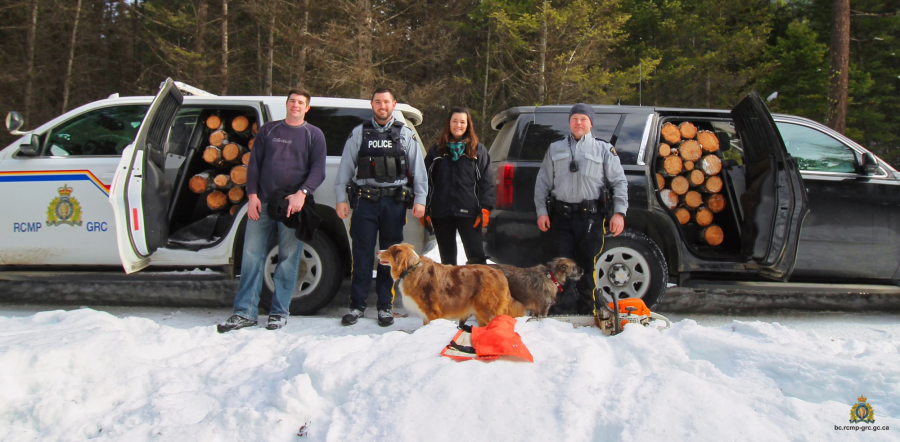 <who>Photo Credit: RCMP</who>Cst. Jonathan Stermscheg, Cst. Chris Hansen, PS Leanne McLaren and Cpl. Phil Peters stand in front of two police vehicles full of firewood.